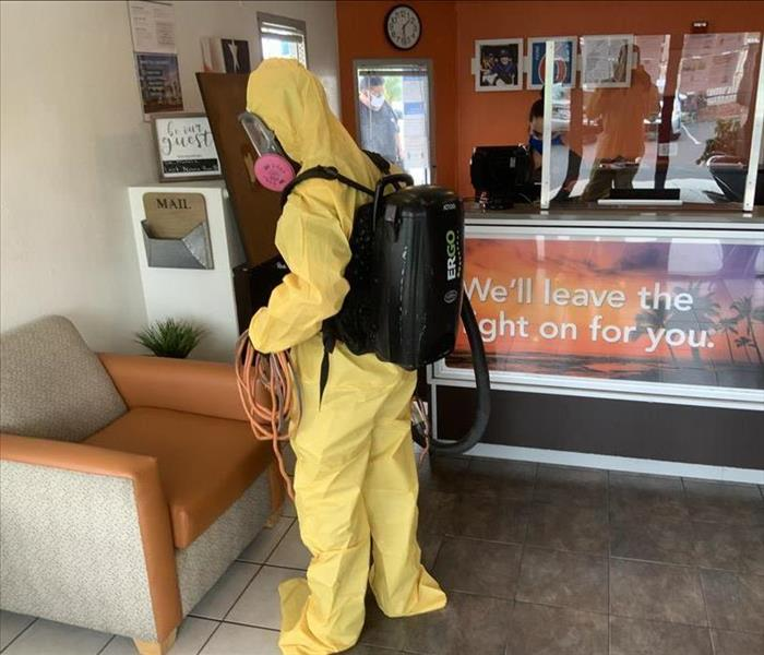 Disinfecting Motel 6 with yellow suit gear