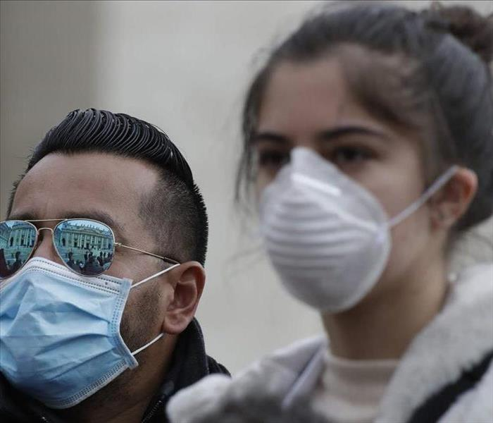 Two people wearing facemasks outside of a building